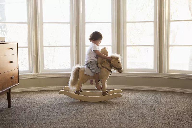 Enfant qui est assis sur son cheval à bascule.